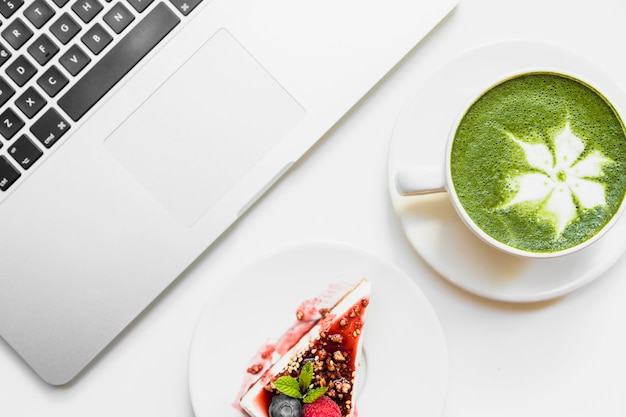 Matcha green tea cup; cheesecake and laptop on white backdrop