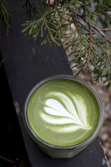 Matcha, green tea in glass cup. grey stone background. close up. top view.
