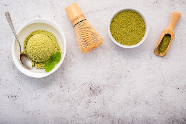 Matcha green tea ice cream with matcha whisk brush setup on white stone background