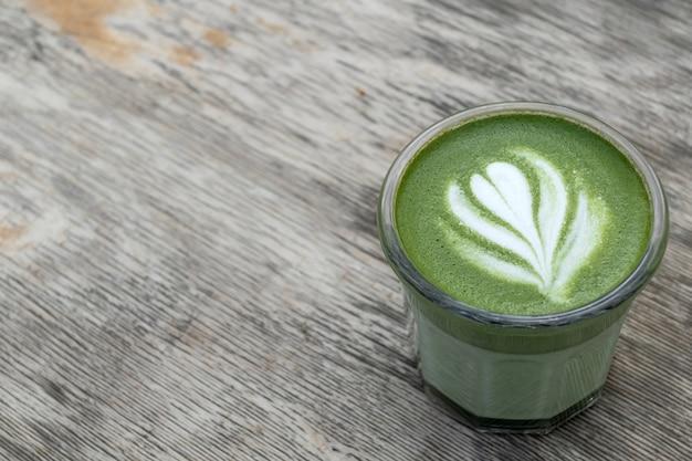 Матча, зеленый чай в стеклянной чашке. серый каменный фон. закройте вверх. вид сверху. место для текста.