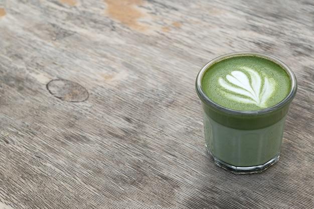 Матча, зеленый чай в стеклянной чашке. серый каменный фон. закройте вверх. вид сверху. место для текста. Premium Фотографии