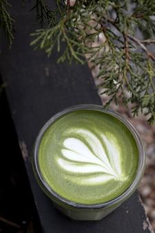 Матча, зеленый чай в стеклянной чашке. серый каменный фон. закройте вверх. вид сверху.