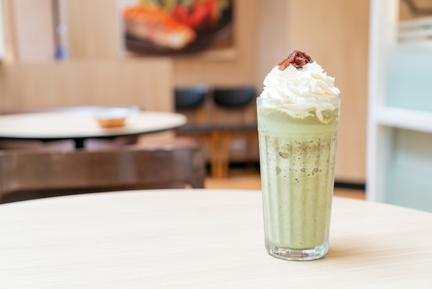 Matcha green tea latte blended with whipped cream and red bean in coffee shop cafe and restaurant