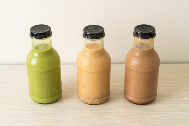 Matcha green tea latte, chocolate and milk tea with pudding jelly in glass bottle on the table