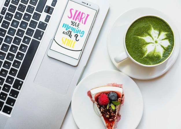 抹茶ラテカップチーズケーキと白い机の上の開いているラップトップ上の朝のメッセージと携帯電話