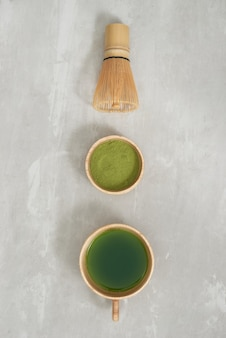 Matcha green tea latte in a cup and tea ceremony utensils with german cake. copy space