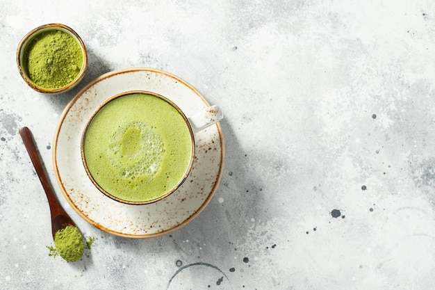 Matcha green tea latte in a cup with cream.