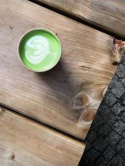 Matcha green tea latte in disposable cardboard takeaway cup on rustic wooden table outdoors