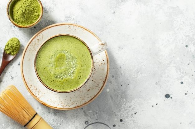 Латте зеленый чай матча в чашке со сливками.