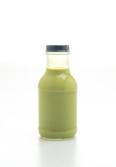 白で隔離のガラス瓶の抹茶緑茶ラテ