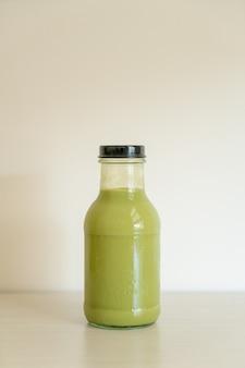 テーブルの上のガラス瓶に抹茶緑茶ラテ