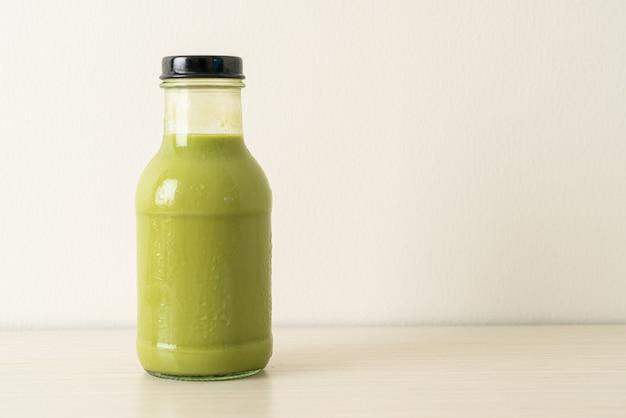 Латте зеленый чай матча в стеклянной бутылке на столе