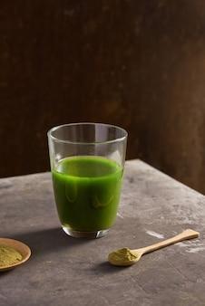 Матте зеленый чай латте в стеклянной чашке