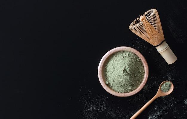 Матте зеленый чай латте на черном столе Premium Фотографии