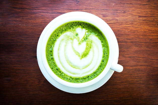 Matcha green tea latte with heart shape latte art in white cup on wooden table