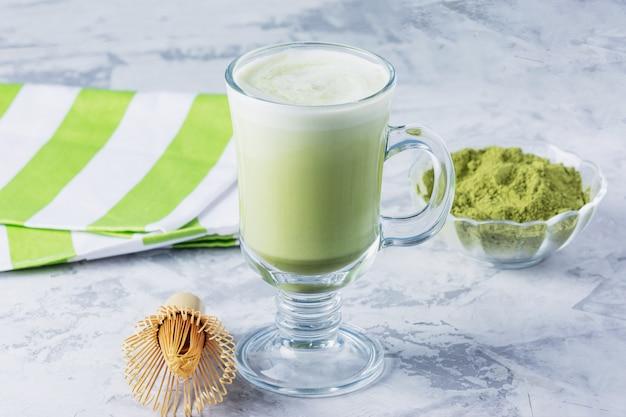 Матте зеленый чай латте с порошком матча и бамбуковым венчиком. здоровый напиток в прозрачном стакане крупным планом