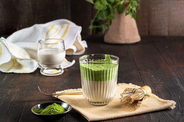 Matcha green tea latte with matcha powder and bamboo whisk