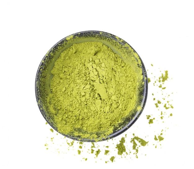 Matcha, green tea powder in black bowl on white
