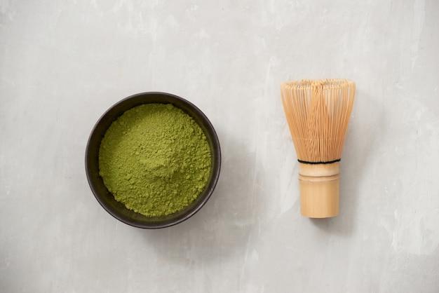 スレートの背景に竹の泡立て器で黒いボウルに抹茶、緑茶粉末。上面図。