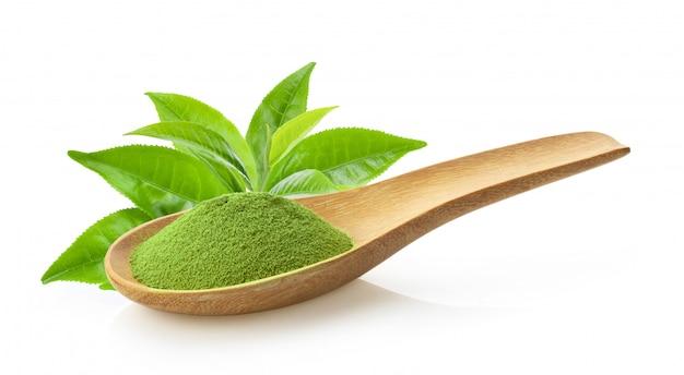 Порошок зеленого чая matcha в деревянной ложке с листом на белом