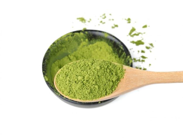 Порошок зеленого чая матча в деревянной ложке на белом