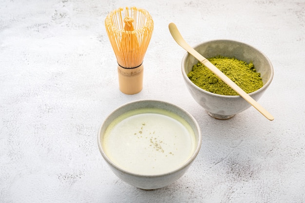 Matcha green tea powder with bamboo matcha whisk brush setup on white concrete background