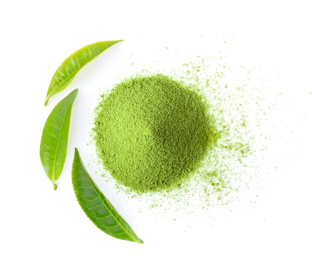Matcha green tea powder with leaves on white wall.