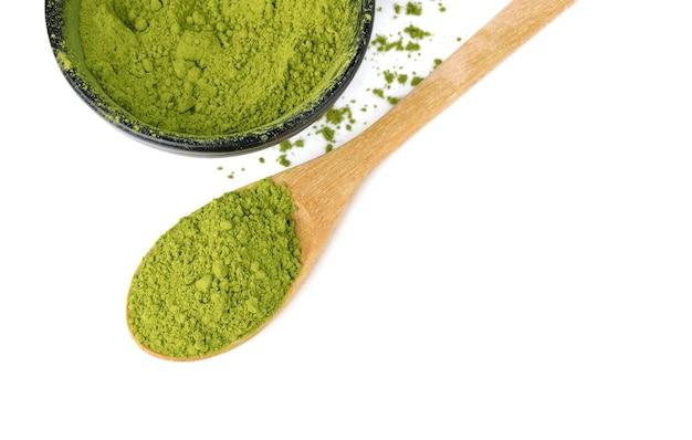 Порошок зеленого чая матча с деревянной ложкой, изолированные на белом пространстве