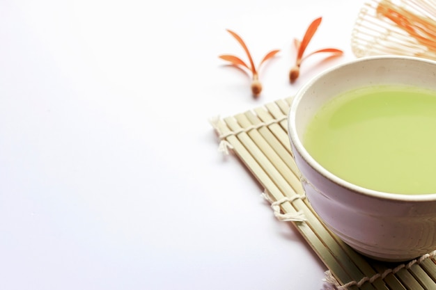 Matcha green tea on white wood with soft-focus in the background. over light