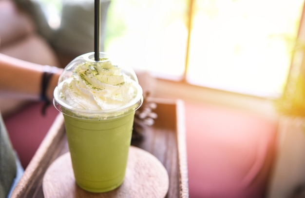 Зеленый чай матча с молоком в пластиковом стакане, поданный в кафе