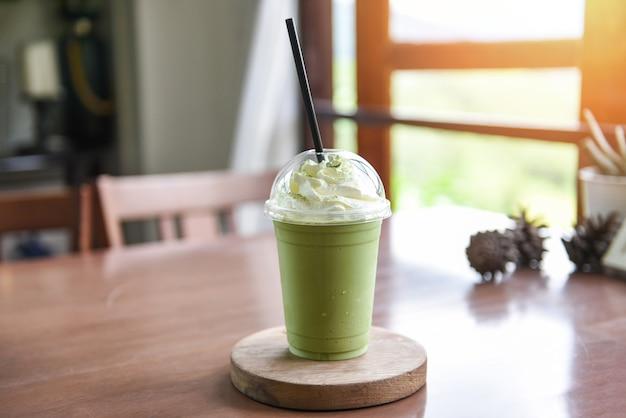 Зеленый чай матча с молоком на пластиковом стакане в кафе
