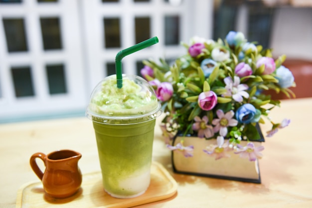 Matcha green tea with milk on plastic glass on the table in a cafe