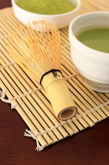 Matcha green tea on wood table with warm fall colors in soft-focus in the background.