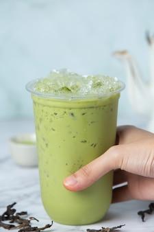 Ледяной зеленый чай матча на мраморном полу. это вкусный и питательный.