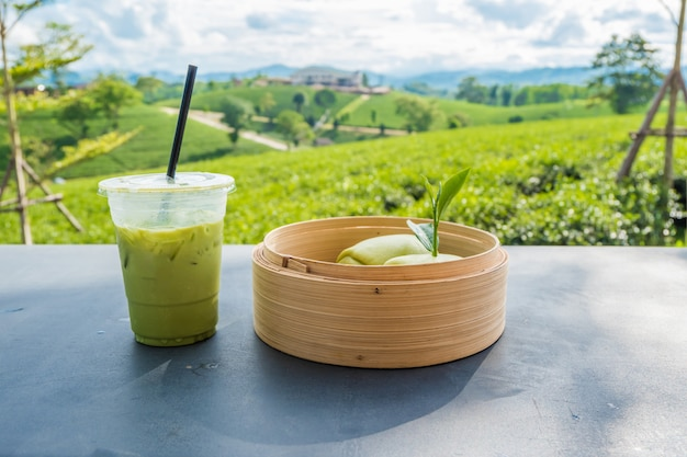 Matcha iced green tea in clear plastic glass and steamed bun table with tea plantation background