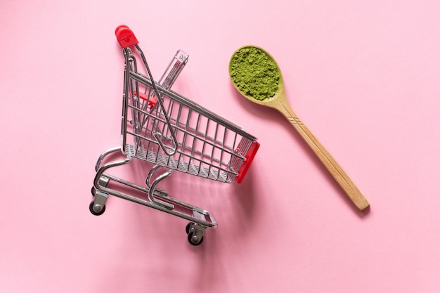 Matcha. japanese powdered green tea in a spoon on a pink background.  shopping cart trolley.