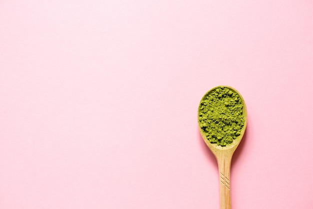 Matcha. japanese powdered green tea in a spoon on a pink background.