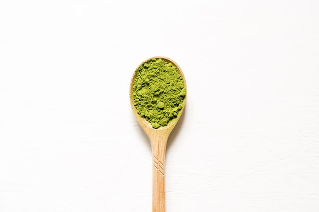 Matcha. japanese powdered green tea in a spoon on a white background. top view and copy space.