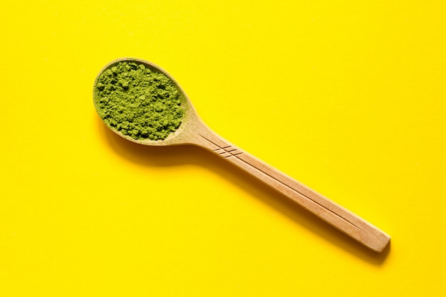 Matcha. japanese powdered green tea in a spoon on a yellow background.