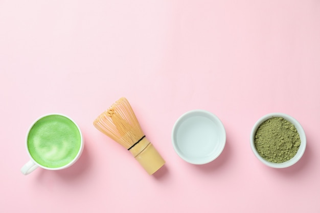 Матча латте и аксессуары для приготовления на розовом фоне