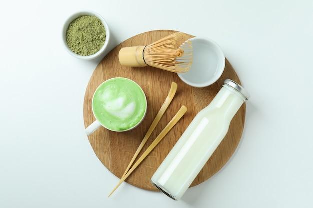 Матча латте и аксессуары для приготовления на белом фоне