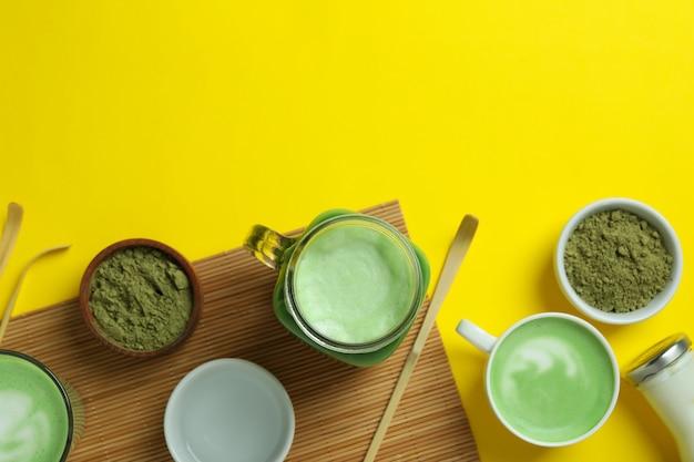 Матча латте и аксессуары для приготовления на желтом фоне
