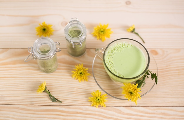 Matcha latte in a cup with matcha powder