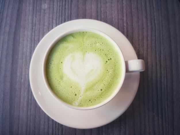 Matcha latte green tea foam art is heart in a brown cup