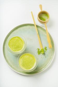 抹茶パウダー、竹スクープ茶杓、ストレーナーで飾られたセラミックトレイの抹茶ラテヘルシーコーヒー代替品。フラットレイ。上面図