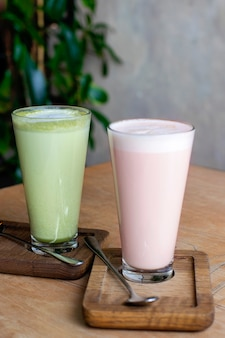 Matcha latte and raspberry latte in a glass.