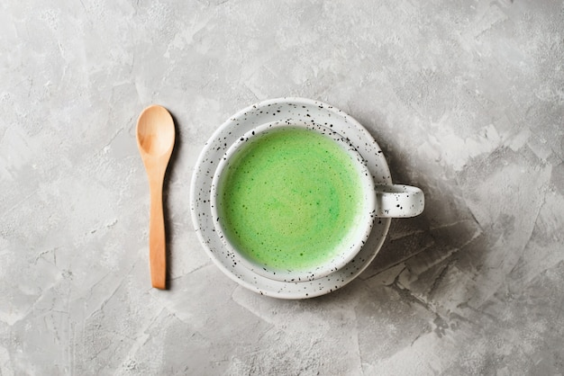 Matcha latte in white cup close up over grey background