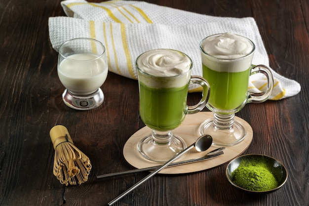Matcha latte with cream foam in glasses and bamboo whisk