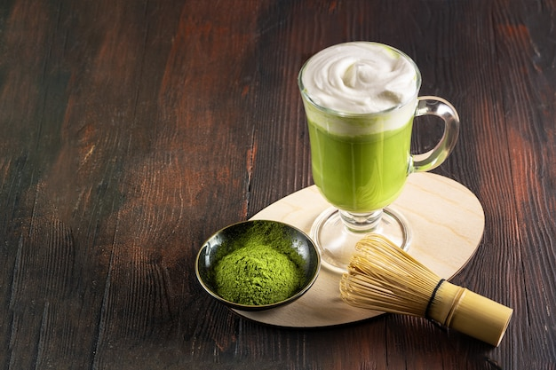 竹泡立て器と抹茶パウダーの近くのグラスにクリームの泡が入った抹茶ラテ