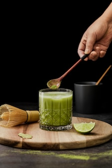 Matcha tea in glass with lime and bamboo whisk
